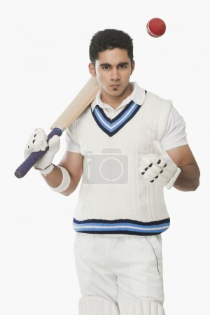 Photo for Cricket batsman holding a bat and tossing a ball - Royalty Free Image