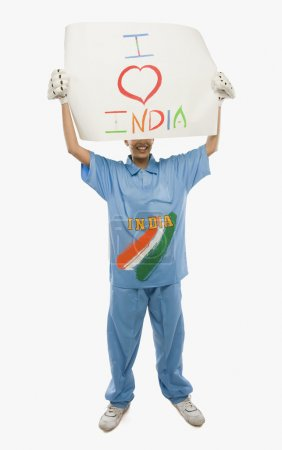 Woman in cricket uniform holding a placard