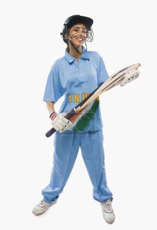 Female cricketer holding a cricket bat