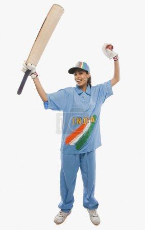 Female cricketer raising bat