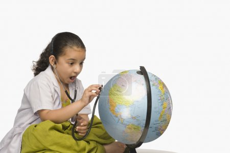 Girl examining a globe with a stethoscope
