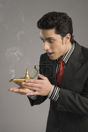 Businessman scratching a magic lamp