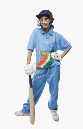 Female cricketer standing with a cricket bat