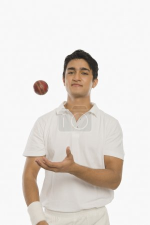 Photo for Bowler tossing a cricket ball against white background - Royalty Free Image