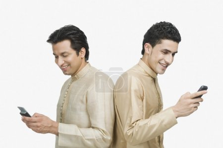 Two men text messaging on mobile phones