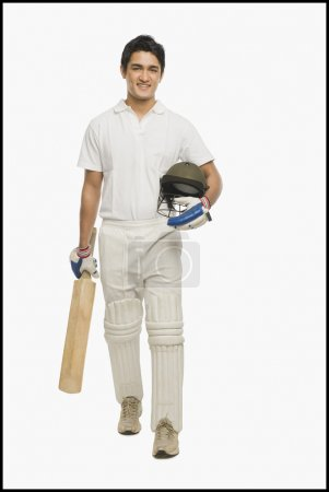 Cricket batsman walking with a bat and a helmet