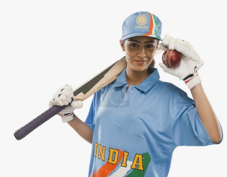 Female cricketer holding a cricket bat and a ball