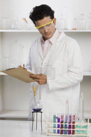 Scientist writing on a clipboard in a laboratory