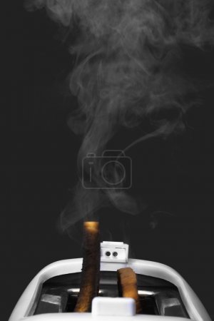Photo for Close-up of toasts burning in a toaster - Royalty Free Image