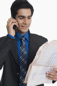Real estate agent holding a blueprint and talking on a mobile phone