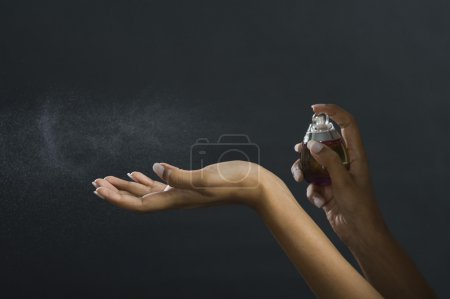 Photo pour Femme appliquant le parfum sur sa main - image libre de droit