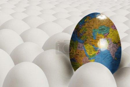 Egg with image of earth among plain white eggs