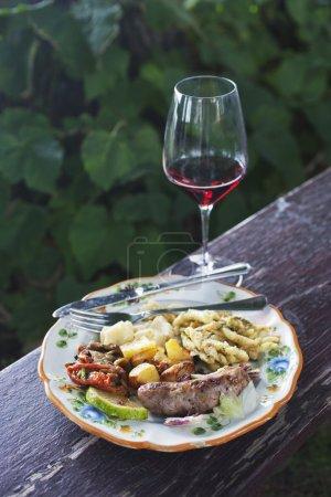 Mahlzeit auf einem Teller mit einem Weinglas serviert