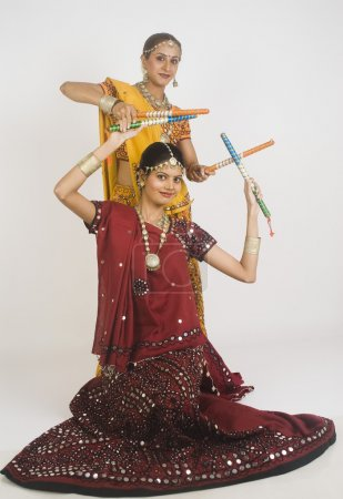 Two women performing dandiya