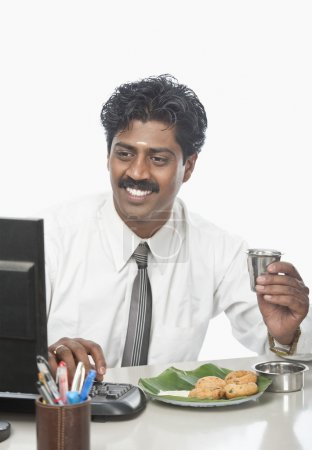 Businessman working in an office and having food