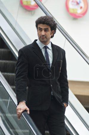 Businessman moving down on an escalator