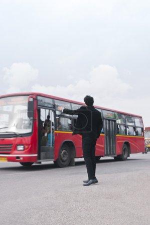 Businessman hailing bus at roadside