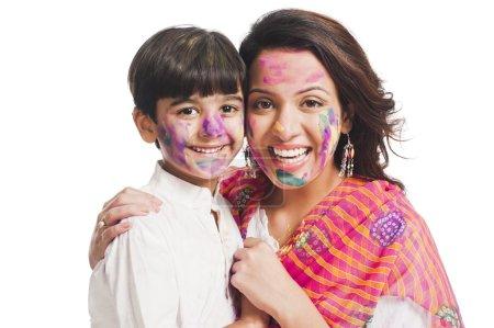 Photo pour Portrait d'une femme avec son fils célébrant le festival Holi - image libre de droit