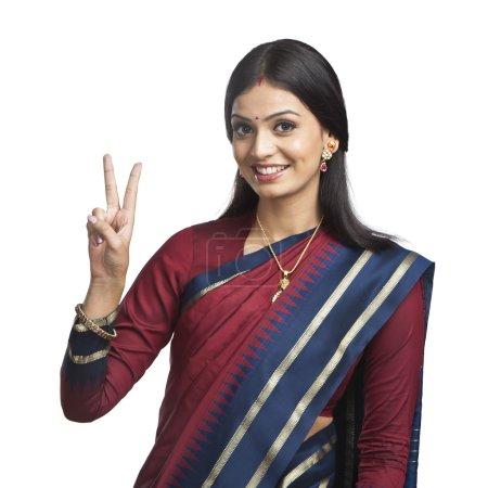 Photo pour Traditionnellement indienne femme gesticulant signe de victoire - image libre de droit