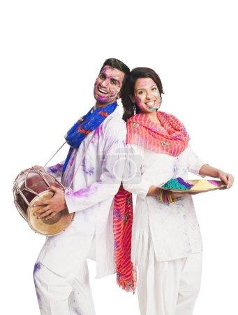 Photo pour Couple célébrant Holi avec des couleurs et un tambour - image libre de droit