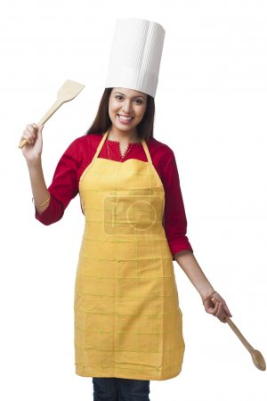 Woman holding a spatula and ladle