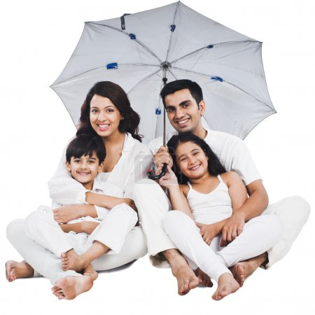 Family sitting under an umbrella