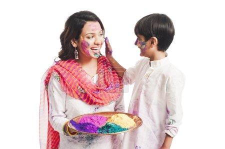 Photo pour Femme célébrant le festival Holi avec son fils - image libre de droit