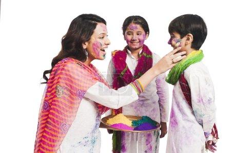 Frau feiert Holi-Fest mit ihren Kindern
