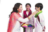 Woman celebrating Holi festival with her children