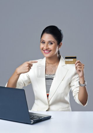 Businesswoman pointing towards a credit card