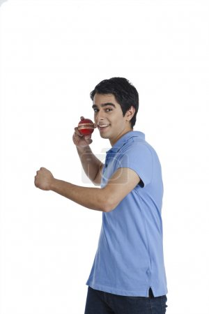 Photo for Man throwing a cricket ball and smiling - Royalty Free Image