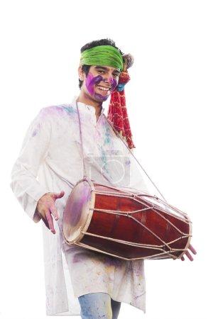 Photo pour Homme célébrant Holi avec le jeu dholak - image libre de droit