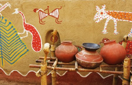 Clay water pots in front of a wall with mural