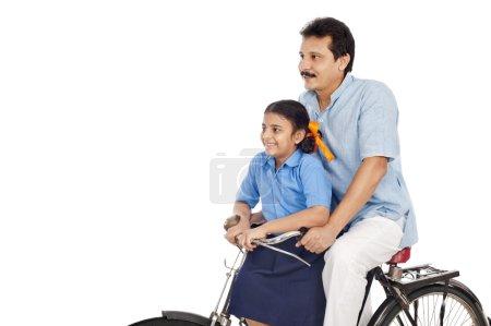 Photo pour Homme avec sa fille sur un vélo isolé sur fond blanc - image libre de droit