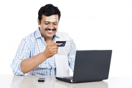 South Indian man doing online shopping with a credit card