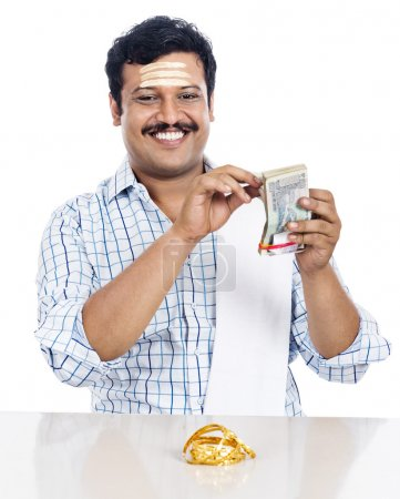 Portrait of a South Indian man counting money and smiling