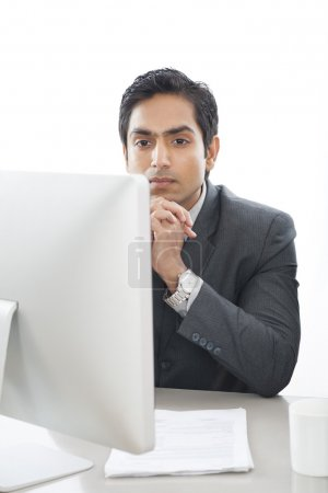 Businessman sitting in front of computer and thinking