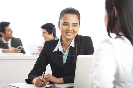 Photo pour Deux femmes d'affaires discutant dans un bureau avec leurs collègues en arrière-plan - image libre de droit