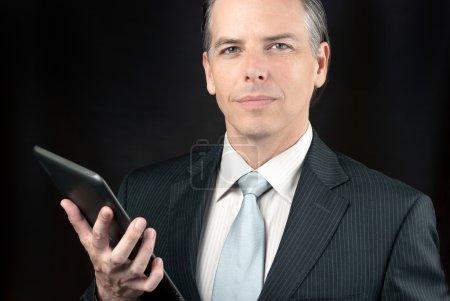 Confident Businessman Holds Tablet