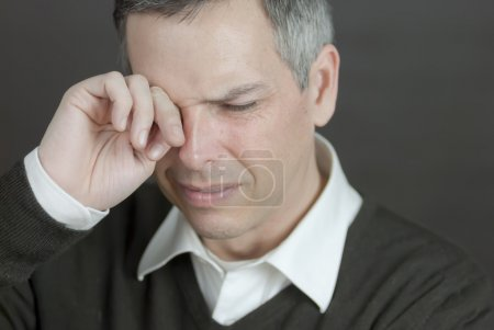 Close-up of a man with a migraine rubbing his eyes...