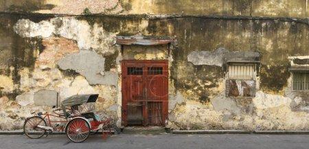 Photo pour Image panoramique d'une vieille porte rouge et d'un trishaw à George Town, Penang, Malaisie - image libre de droit