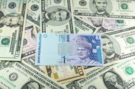 one malaysian ringgit (MYR) on many dollars background