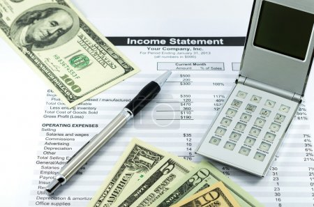 income statement report with calculator, pen and usd money for b