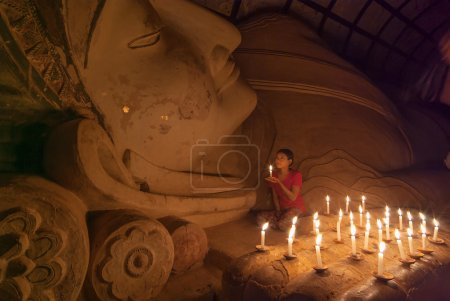 BAGAN, MYANMAR - JAN 5, 2011: Unidentified Burmese girl praying with candle light in a Buddihist temple on January 5, 2011 in Bagan, Myanmar. 89percent of the Burmese population is Buddhist.