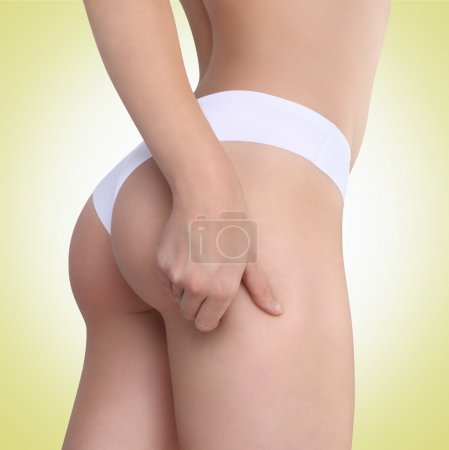 Woman pinches her thigh to control cellulite