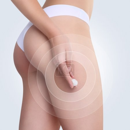 Female applying cosmetic cream from cellulite on the buttocks in
