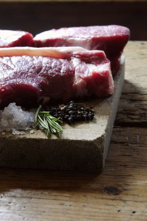 Raw fillet steaks on wooden board