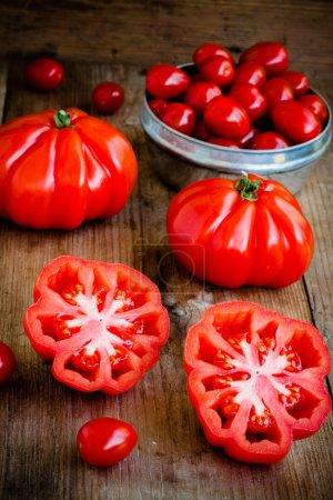 Photo pour Tomates fraîches rouges biologiques et tomates cerises sur fond de bois - image libre de droit