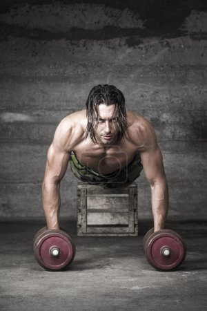 Handsome longh hair athlete pushing up with weights