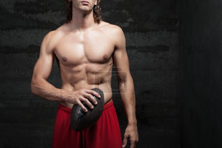 Cropped view of bare chested muscle man holding football ball in his hands